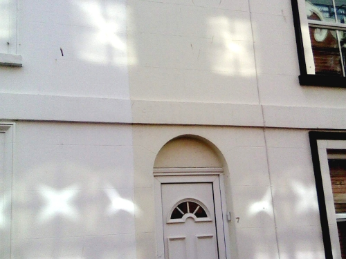 X-shaped reflections of sunlight (some within circles) cast onto the exterior of a house.